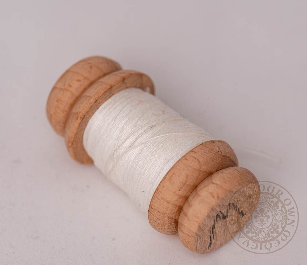 Viking linen thread on a reproduction wooden spool for historical sewing and clothing