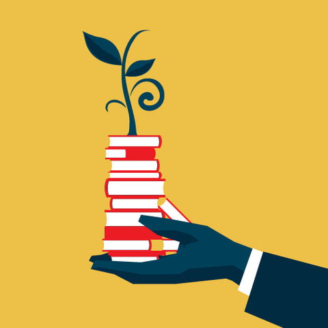 image of a hand holding a pile of books.