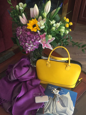 picture composed of a floral arrangement , a design yellow handbag made of leather and an alpaca reversible shawl with two colors purple and grey made of 100% Peruvian alpaca wool