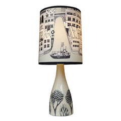 Lush designs creamy off-white ceramic lamp base with black print of little trees shown with lamp shade printed with buildings, river and boat in black