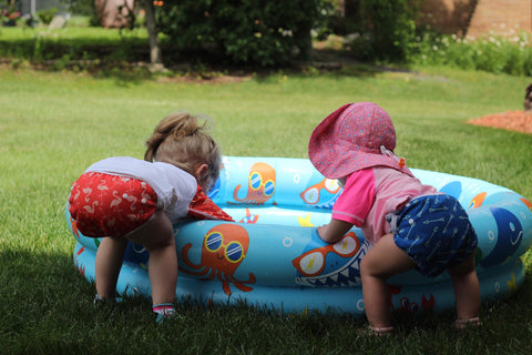 Two girls leaning into a blow up pool in the grass wearing Beau and Belle Littles swim diapers in the flamingo and green arrow prints.