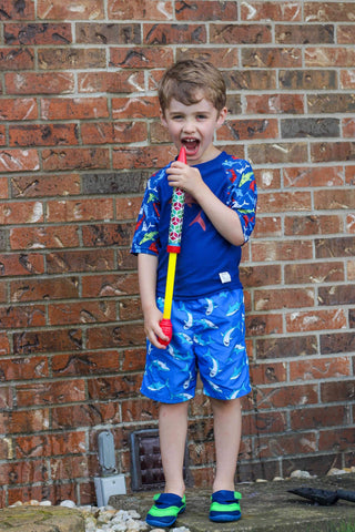 Boy with squirt fun wearing Beau and Belle Littles Shark Rashguard