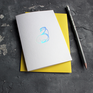 A third birthday card with a hand drawn number three hand pressed in holographic foil on the front