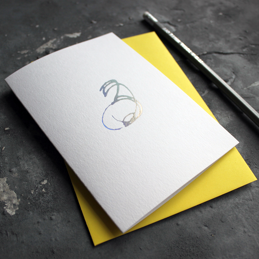 A third birthday card with a hand drawn number three hand pressed in holographic foil on the front and a yellow envelope