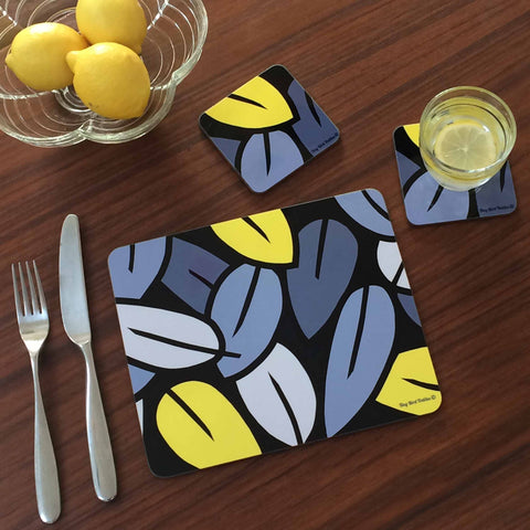 Rectangular table placemat and square drinks mat coaster in grey and yellow Eucalyptus Leaf design, with glass of water and blow of lemons, on dark wood table