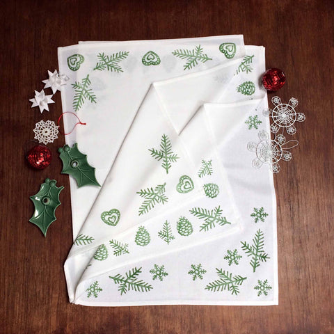 Tiny Bird Textiles Christmas tea towel with green hand lino block printed Scandinavian style snowflake, pine cone, heart design, with Christmas decorations