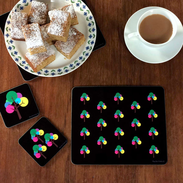 Rectangular Placemat, table mat in modern graphic, repeated Oak Tree design in black, pink, yellow, green, blue, purple, grey with cup of tea, plate of icing sugar dusted cake squares with 2 square coasters with same Oak Tree design, on dark wooden table