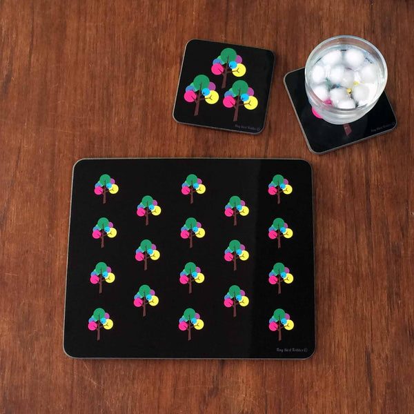 Rectangular Placemat, table mat in modern graphic, repeated Oak Tree design in black, pink, yellow, green, blue, purple, grey with glass of water on square coaster with same Oak Tree design on dark wooden table