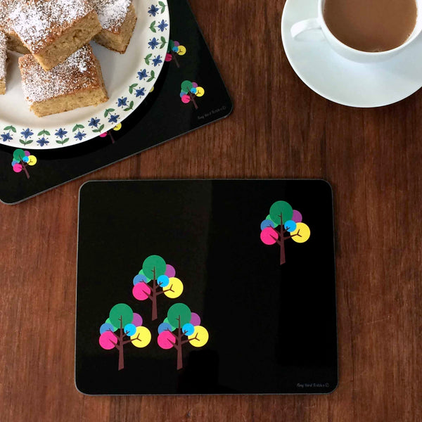 Rectangular Placemat, table mat in modern graphic Oak Tree design with 3 trees in the left corner, 1 tree in the top right corner, in black, pink, yellow, green, blue, purple, grey with a cup of tea and plate of icing sugar dusted cake, on dark wooden table