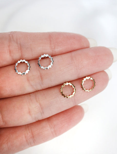 silver and gold scalloped circle studs in hand