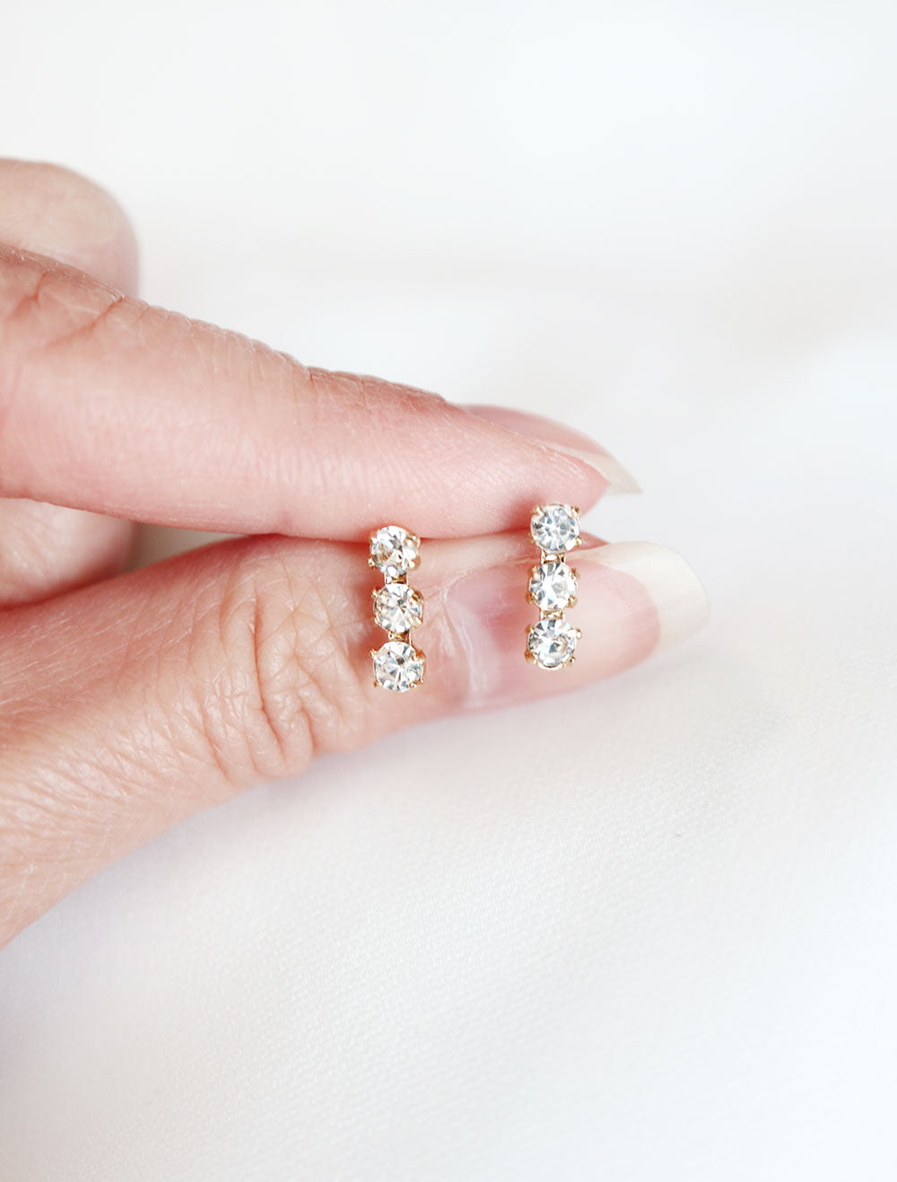 crystal triple bar stud earrings in hand