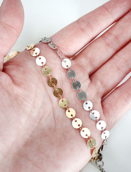 gold and silver large disc chain necklaces in hand