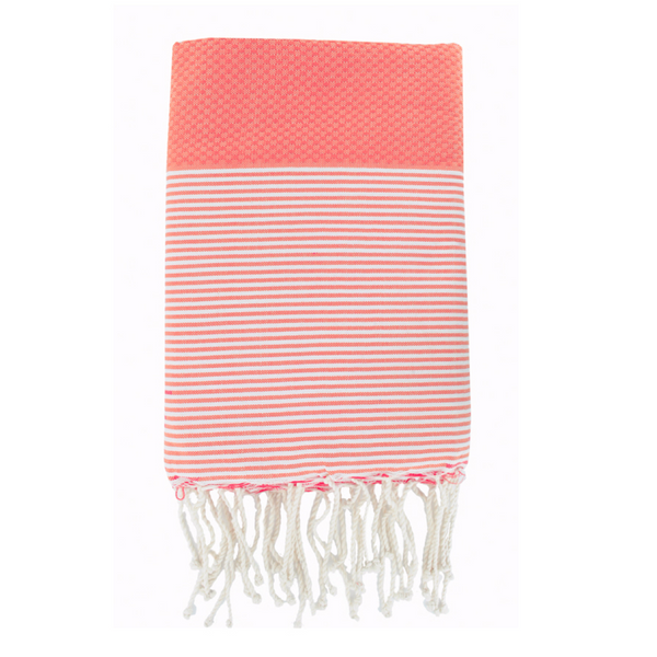 Folded cotton hammam towel with honeycomb weave in coral orange colour with coral/white stripe detail and tassel ends