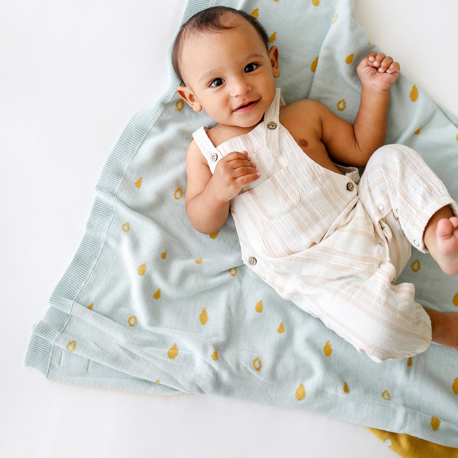 reversible gotc organic cotton blanket with raindrop print in blue and mustard