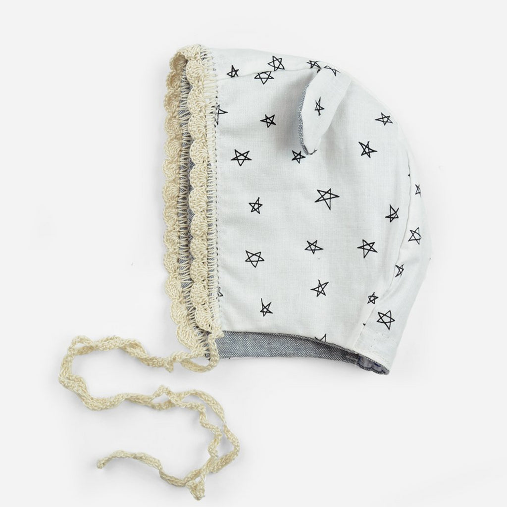 reversible cotton bonnet for babies in chambray and crochet trim and ears with White and black star print fabric