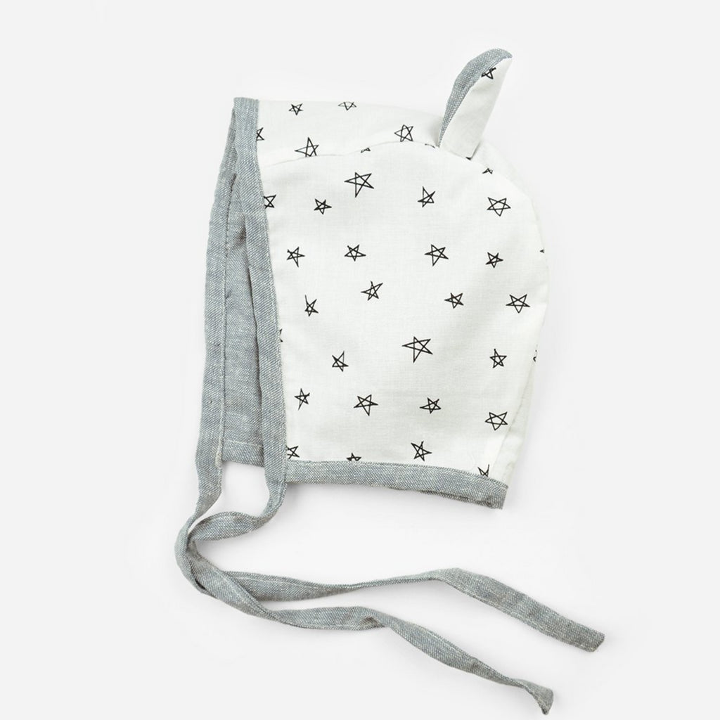 reversible cotton bonnet for babies in chambray  and ears with white with black star print fabric