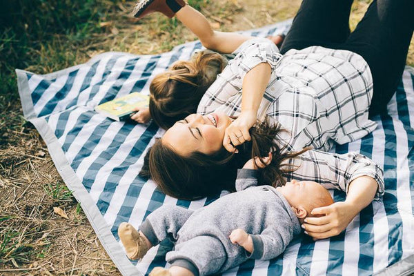 Outdoor Blanket | Navy Gingham - Outdoor Gear - Poshinate Kiddos Baby & Kids Boutique - lying on grass on Navy Gingham blanket