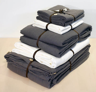 folded stack of 100% linen Cal King bed linen set bed-in-a-bag duvet cover pillow shams bedskirt summer cover sheets off-white white charcoal dark grey colors