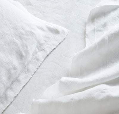 closeup detail of 100% linen raw edge bed set king queen twin sizes with summer cover blanket pillow cases pure white color