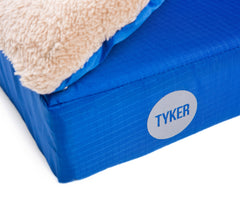 close up of square memory foam blue dog bed with plush cover and reflective tyker logo