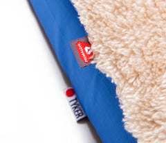close up of a primaloft label on a  square memory foam blue dog bed with plush cover and reflective tyker logo