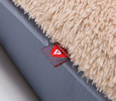 close up of a square memory foam fawn dog bed with plush cover and reflective primaloft logo