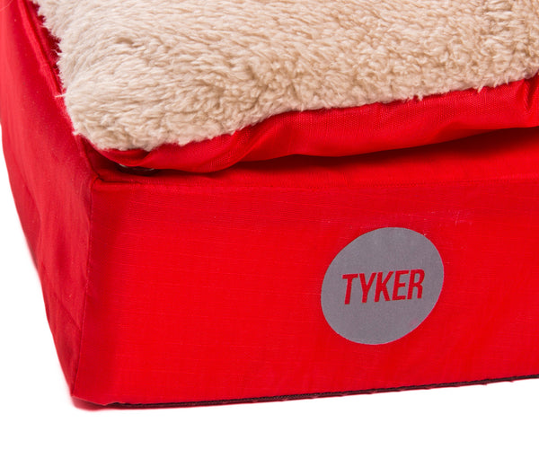 close up of a square memory foam red dog bed with plush cover and reflective tyker logo