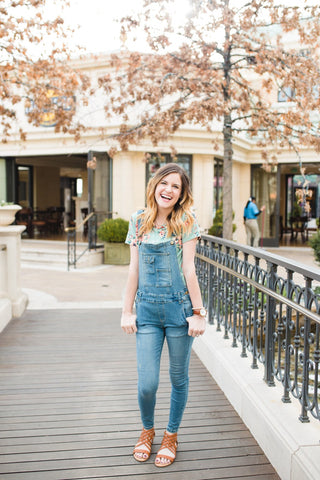 Karli Ellis pairs her overalls with sandals and a floral top