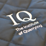 Navy Blue quilted womens bodywarmer with closeup of Institute of Quarrying logo