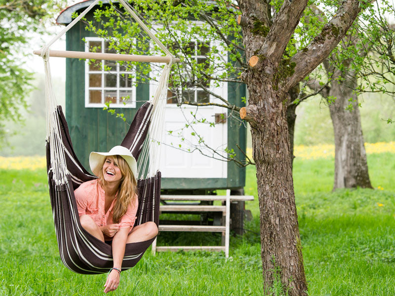 Girl sat in Mocca Brasil Hammock Chair in front of shepherds hut.