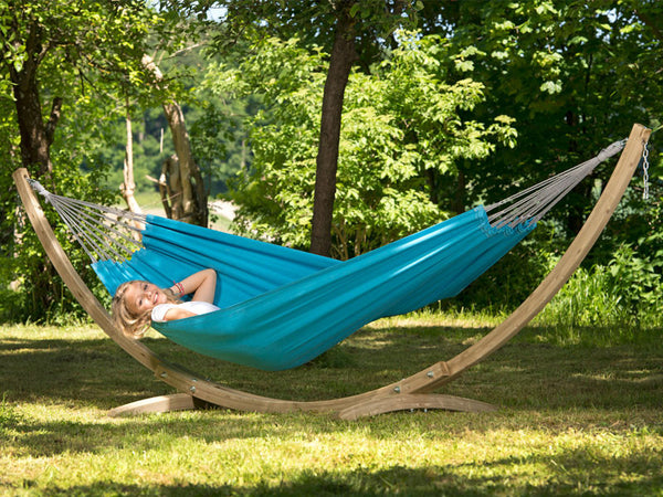 Woman lying in blue Aqua Florida hammock with wooden stand