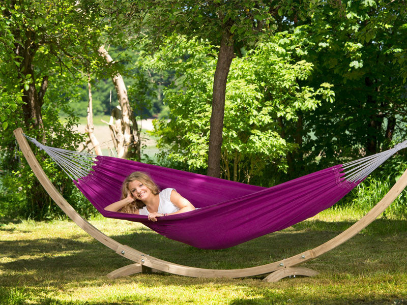 Woman lying in purple Berry Florida hammock with wooden stand