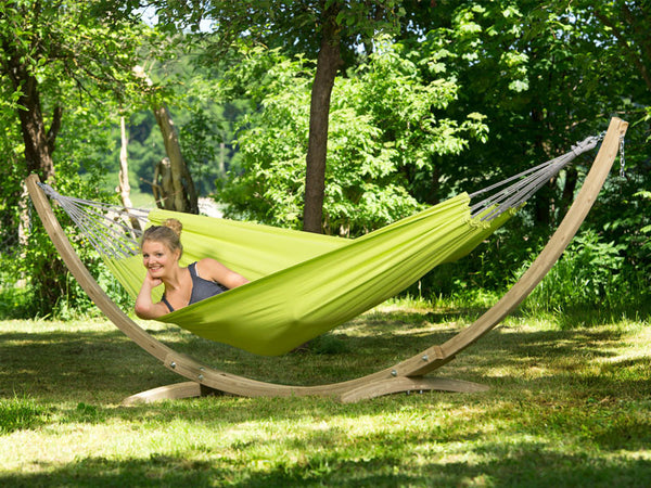 Woman lying in green Kiwi Florida hammock with wooden stand