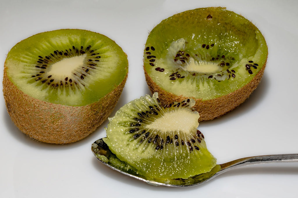 How to cut a kiwi: kiwi halves with the fruit scooped out on a spoon