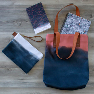 unique handbag featuring indigo clouds and coral sunset design coordinates with our notebooks and zipper clutch bags
