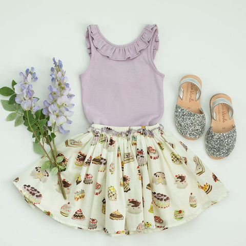 Flatlay image of Gianna skirt with antique white multi desserts print. Paired with purple Princess Diana tank. Silver glitter sandals and purple flowers.