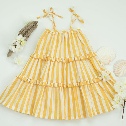 Garden dress in yolk yellow and white stripe dress. With seashells and beach wood accessories.