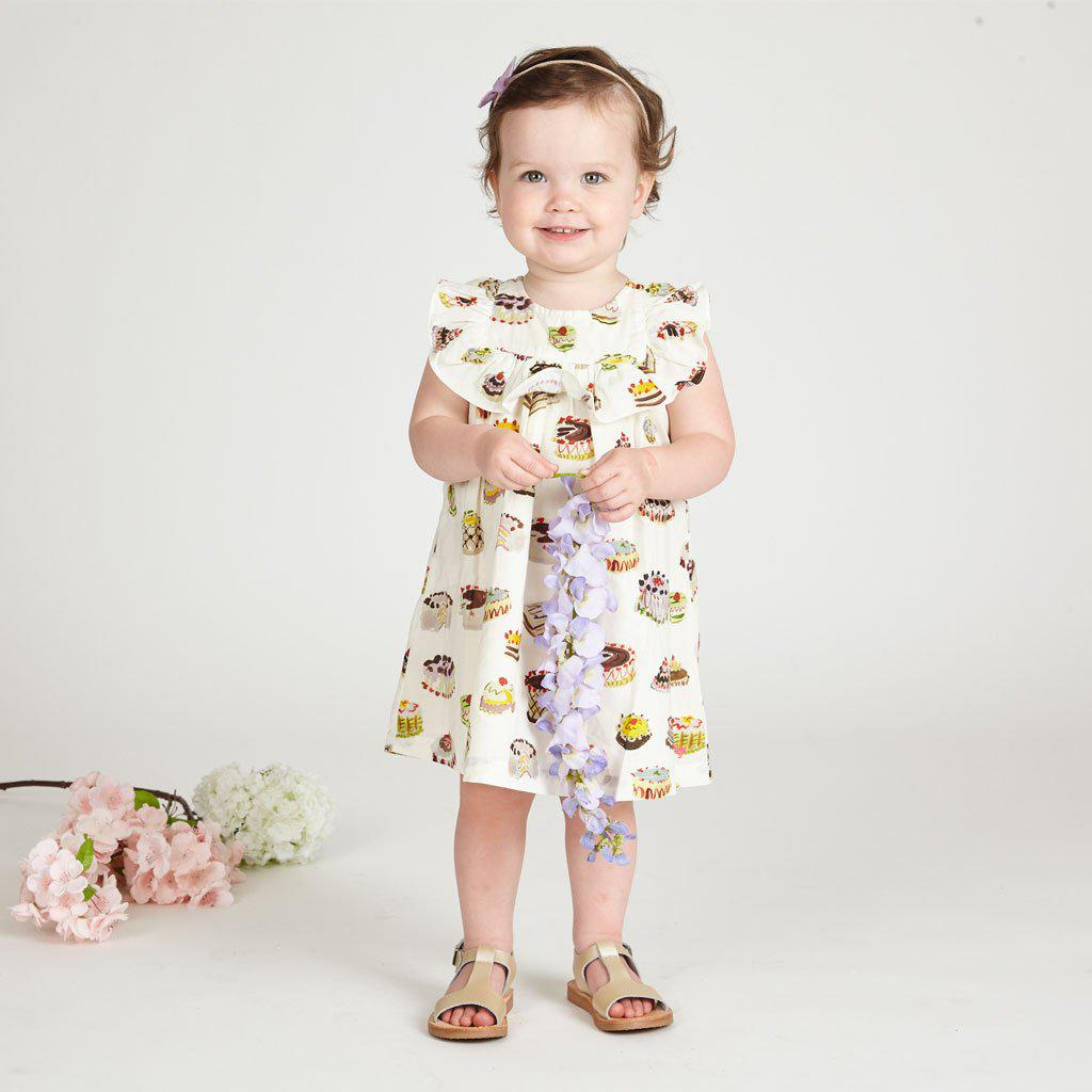 Baby girl smiling in her PC Quinn dress with multi-dessert print.