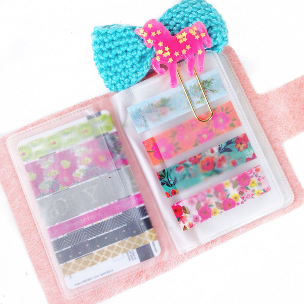 opened light pink washi tape wallet with washi tape samples, hot pink unicorn paper clip, and blue crocheted bow paper clip