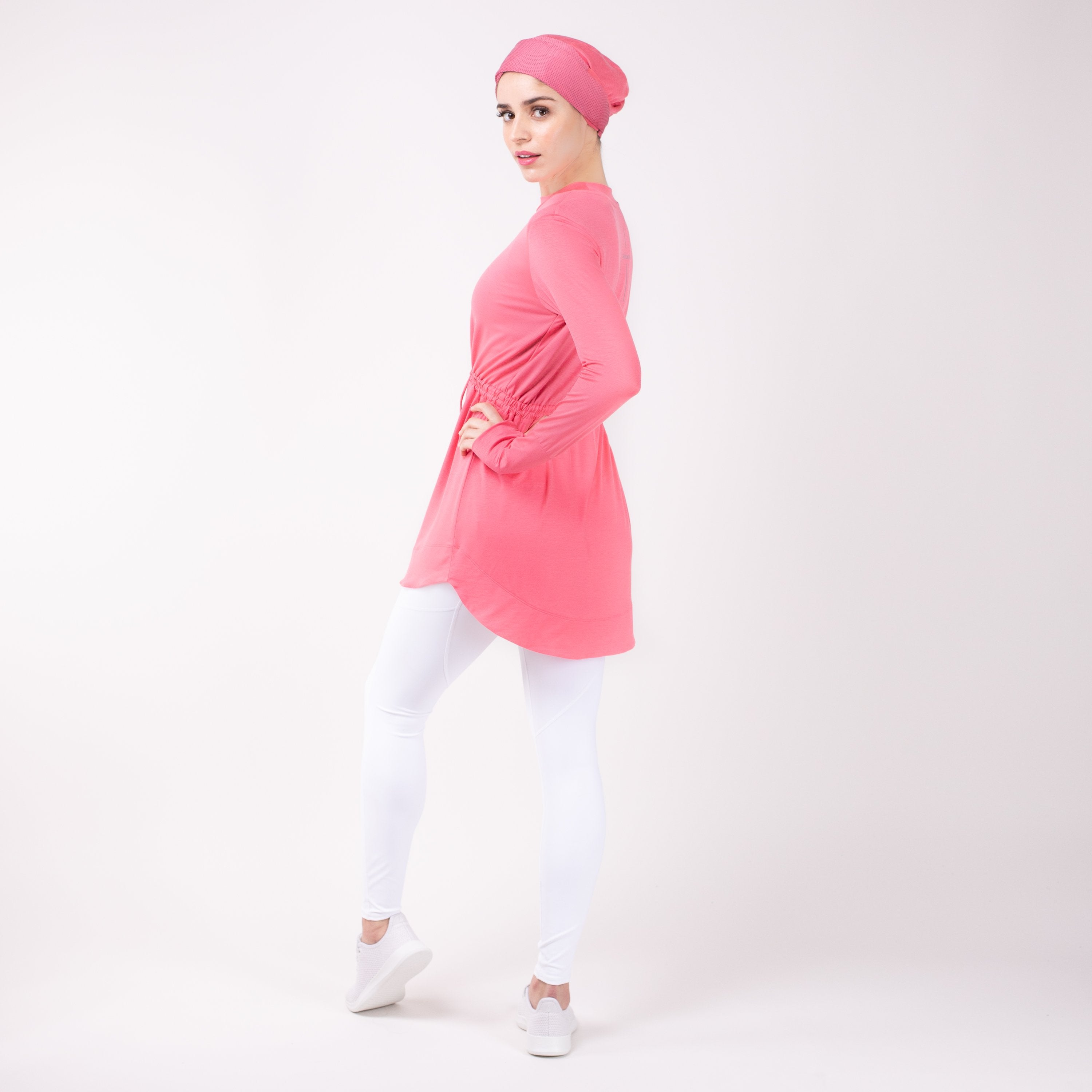 Back of woman standing with one leg bent wearing the modest, berry pink HAWA drawstring tee shirt and white leggings in front of a white back drop.