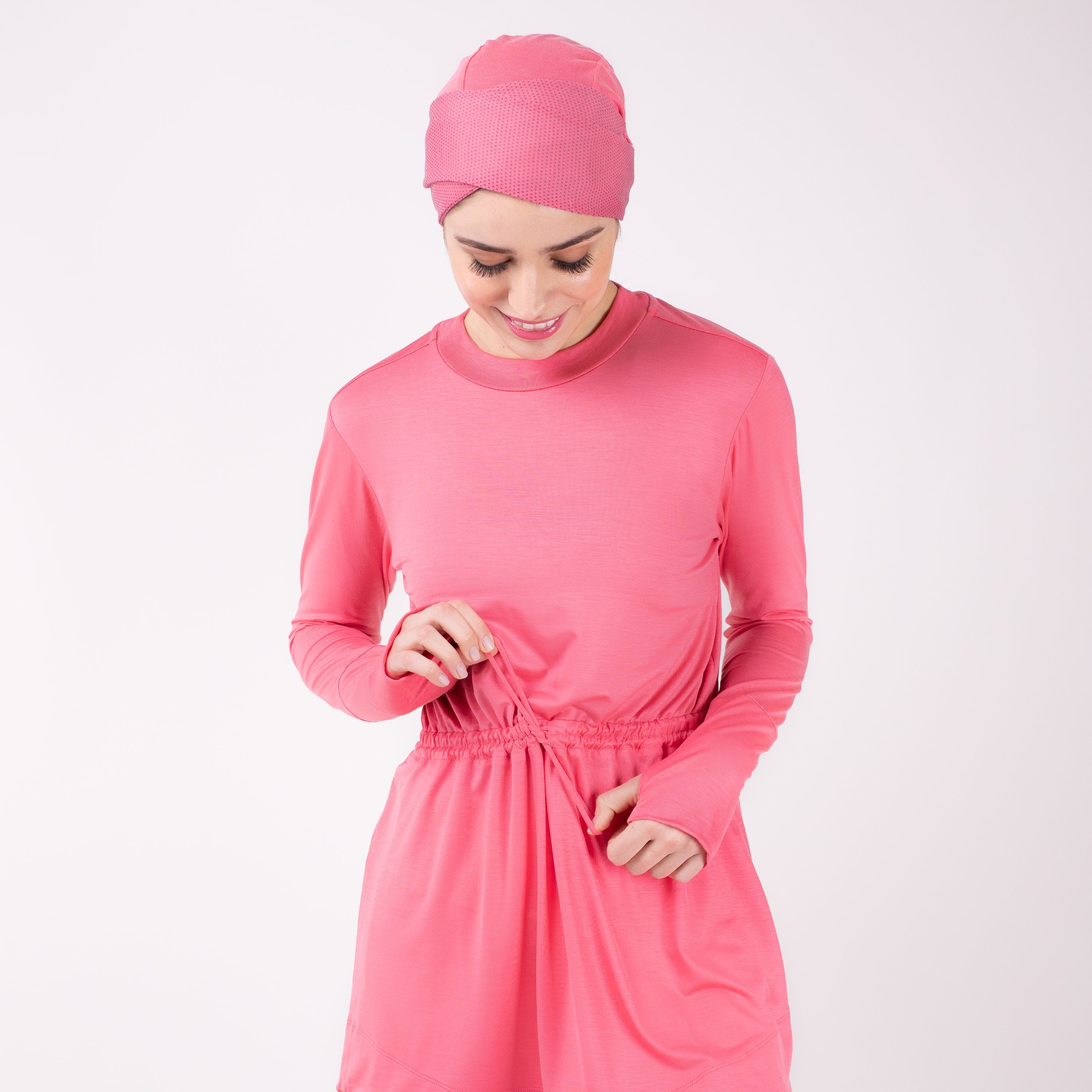 Close up of woman tying the modest, berry pink HAWA drawstring tee shirt with her head bent against a white back drop.