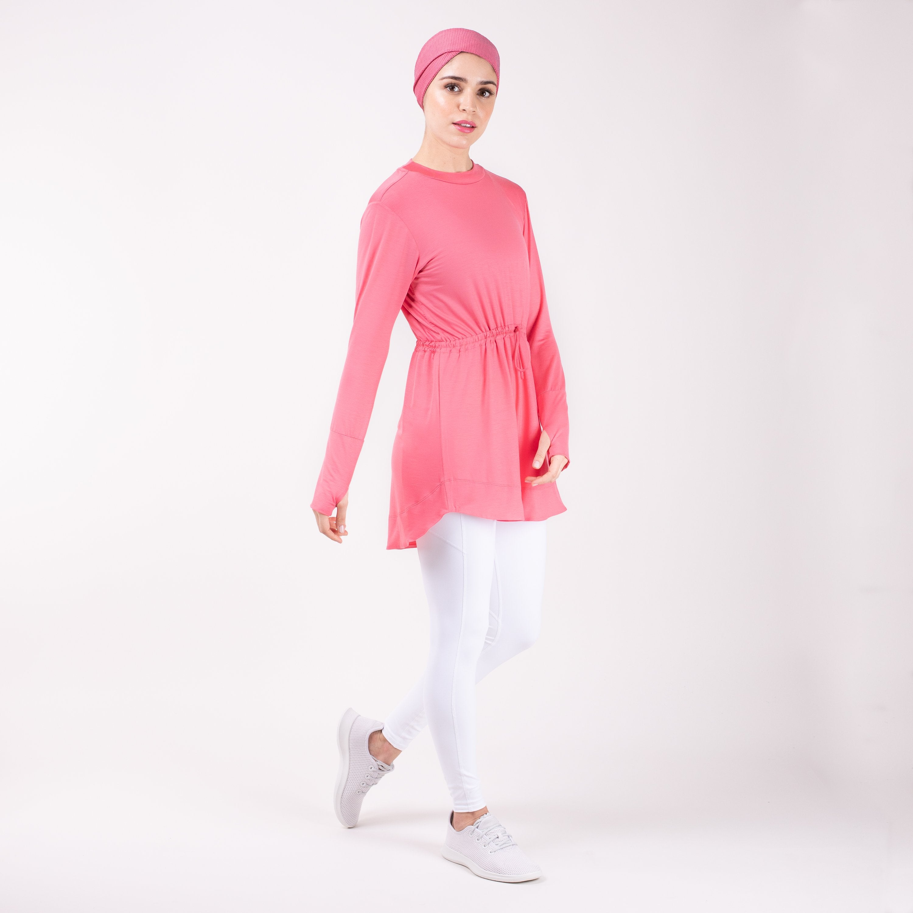 Woman walking to the right wearing the modest, berry pink HAWA drawstring tee shirt and white leggings in front of a white back drop.