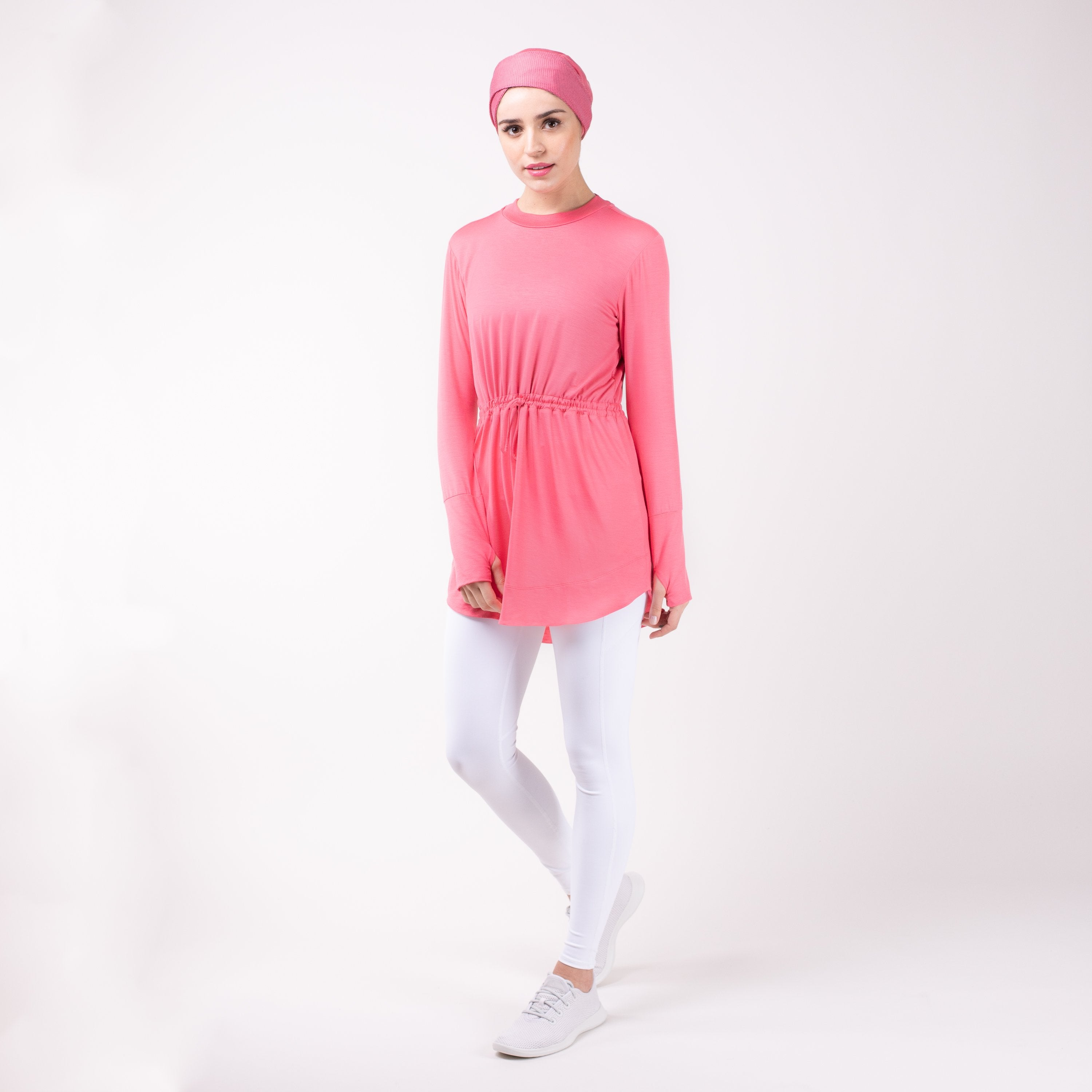 Woman standing with one leg bent wearing the modest, berry pink HAWA drawstring tee shirt and white leggings in front of a white back drop.