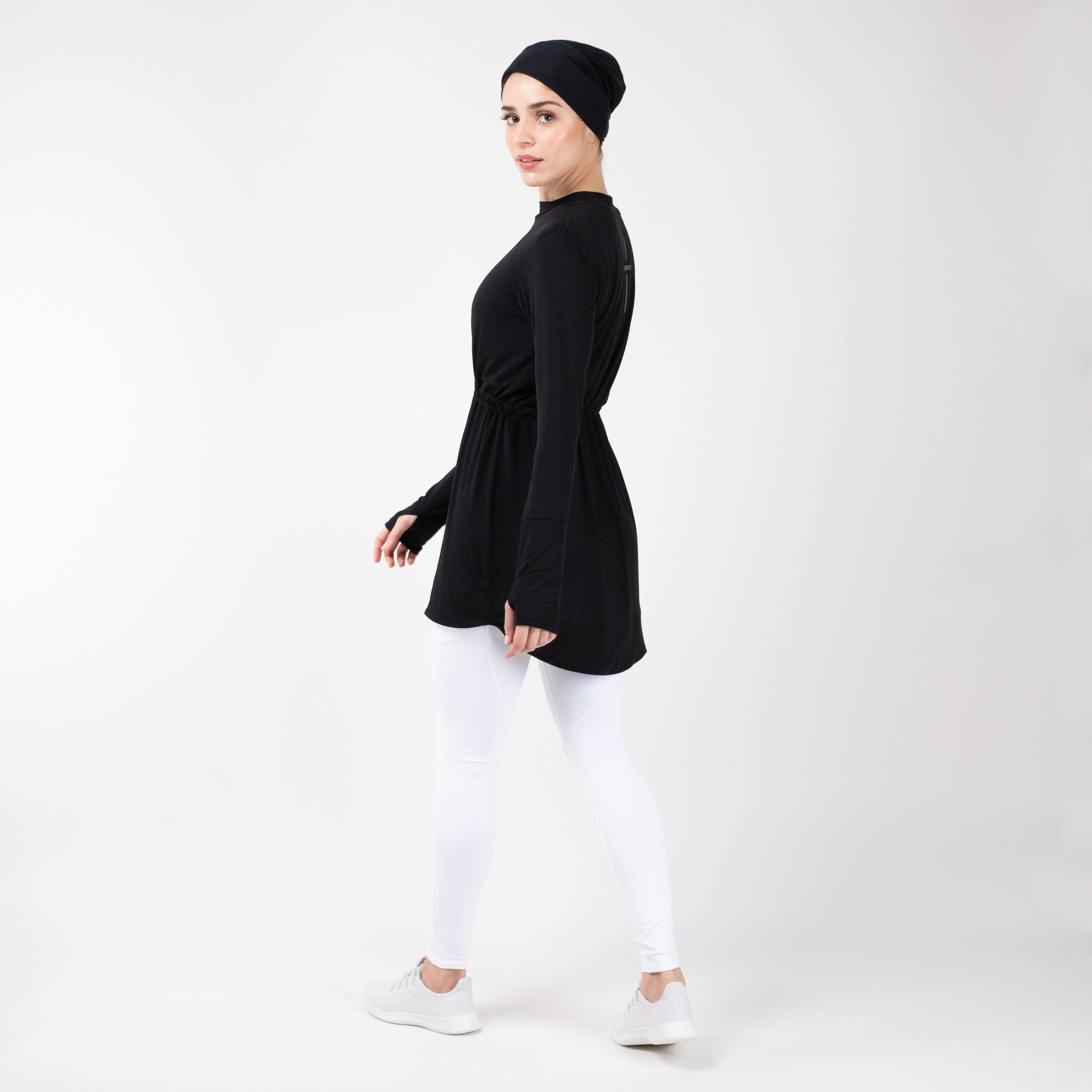 Woman turned to the left side in modest, black HAWA drawstring tee shirt and white leggings in front of a white backdrop.