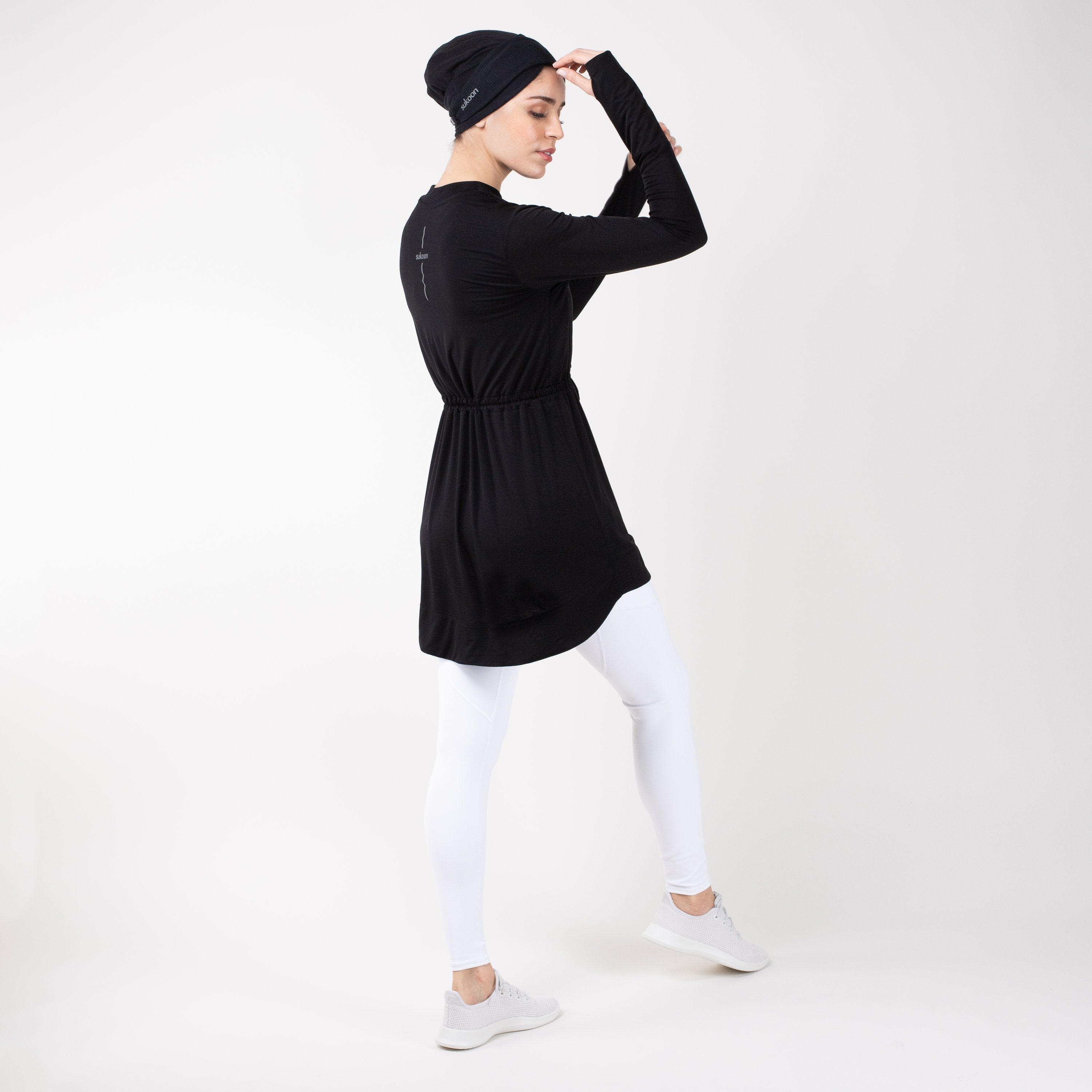 Back of woman in modest, black HAWA drawstring tee shirt and white leggings in front of a white backdrop.