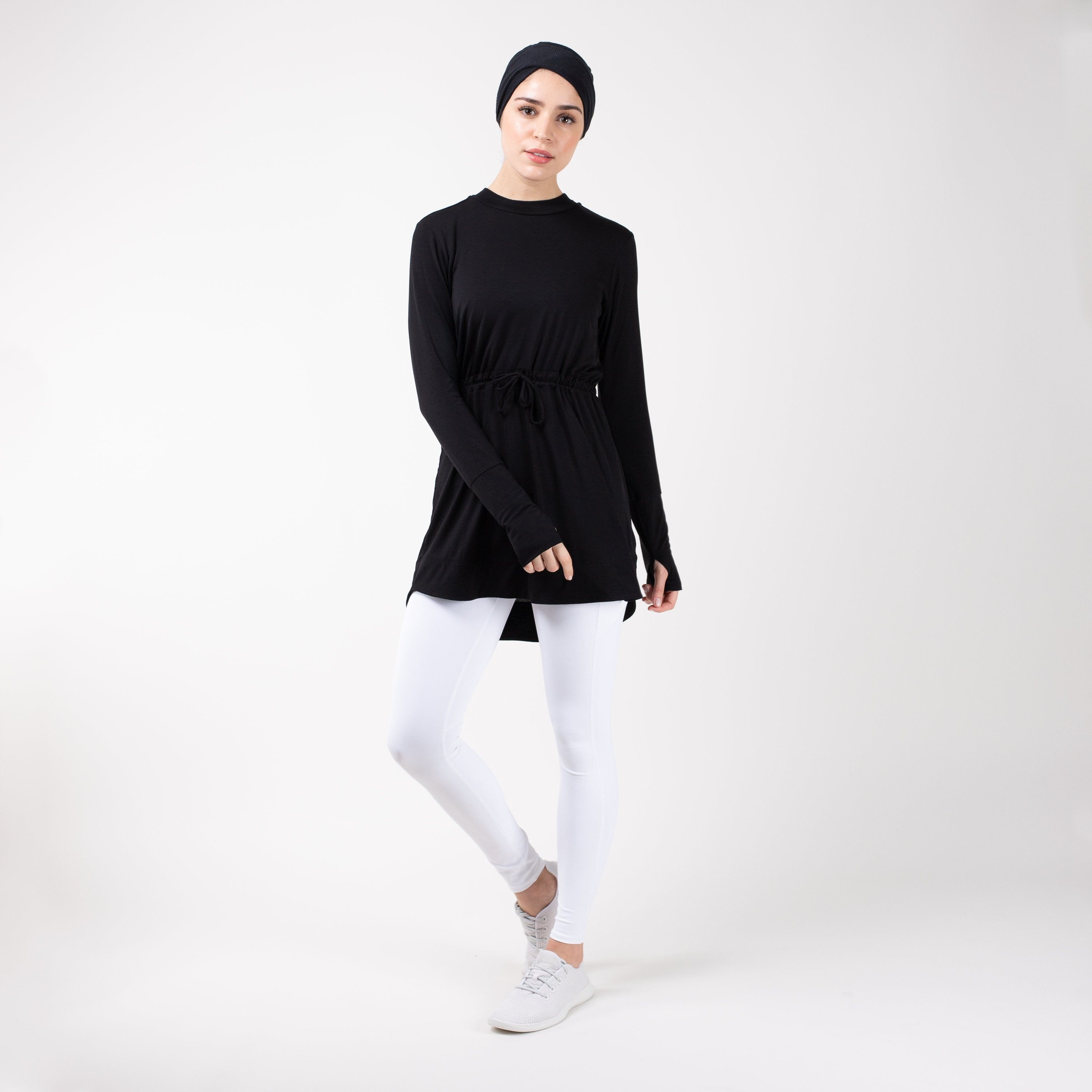 Woman in modest, black HAWA drawstring tee shirt and white leggings in front of a white backdrop.