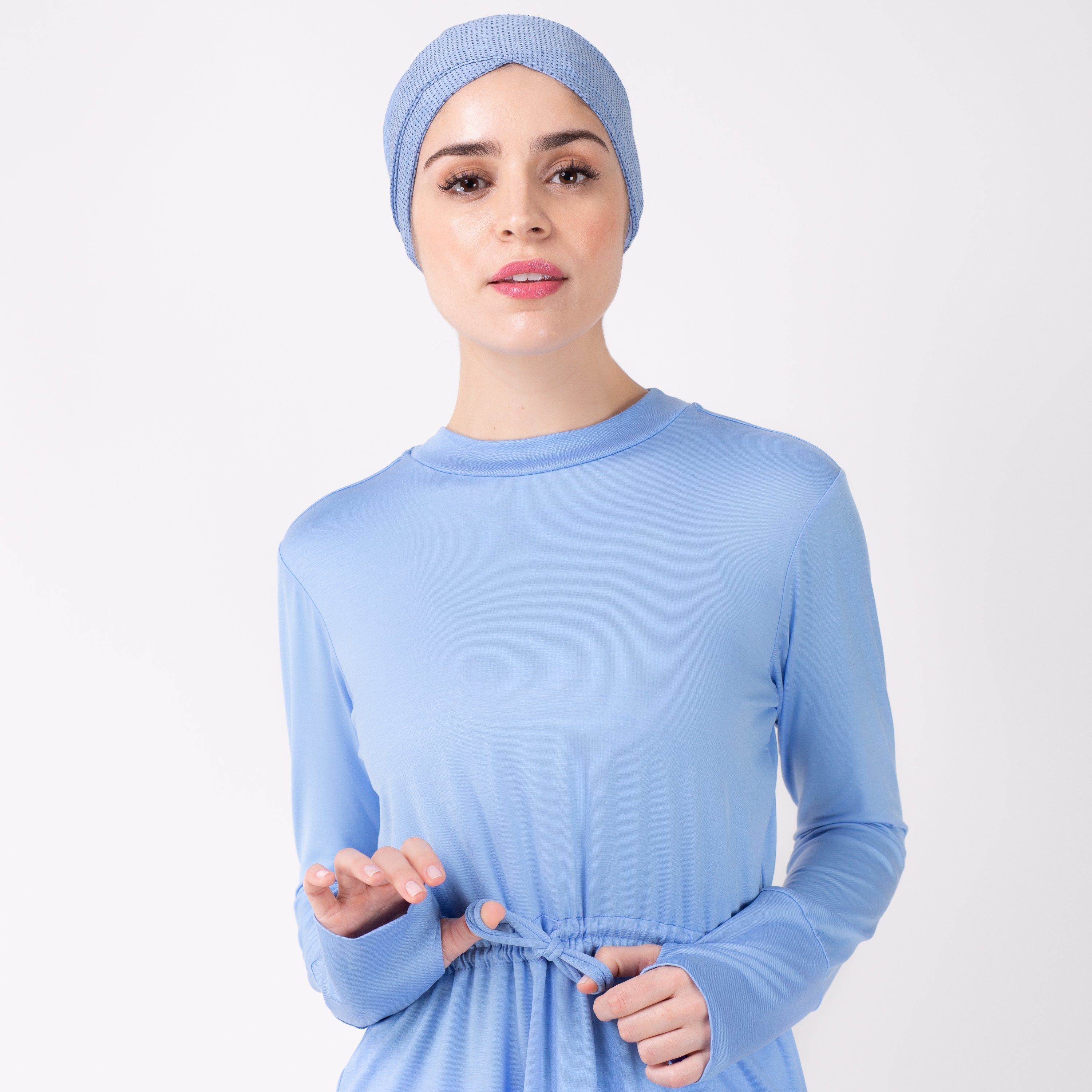 Close up of woman tying the modest, sky blue HAWA drawstring tee shirt against a white back drop.