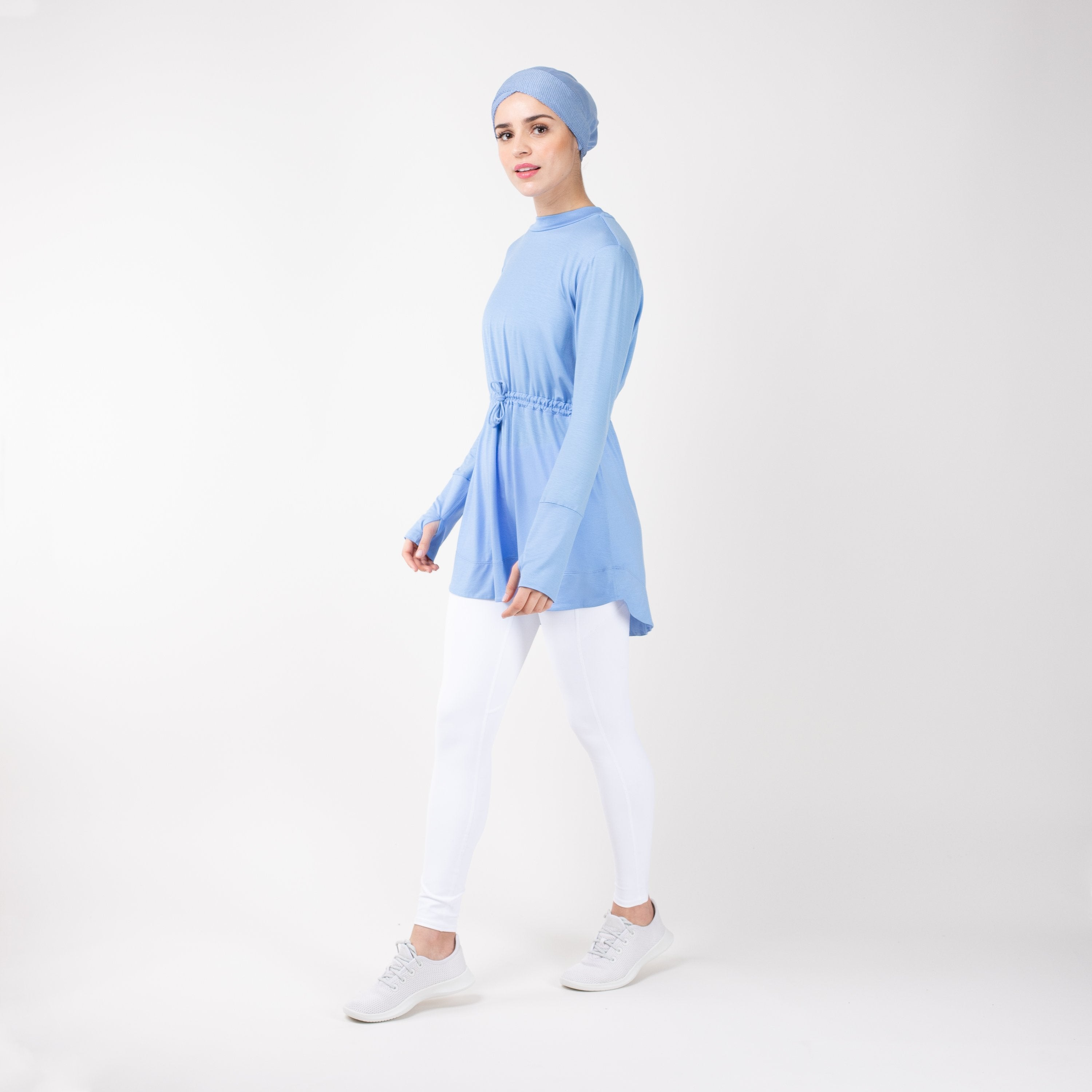 Woman walking to the left wearing the modest, sky blue HAWA drawstring tee shirt and white leggings in front of a white back drop.