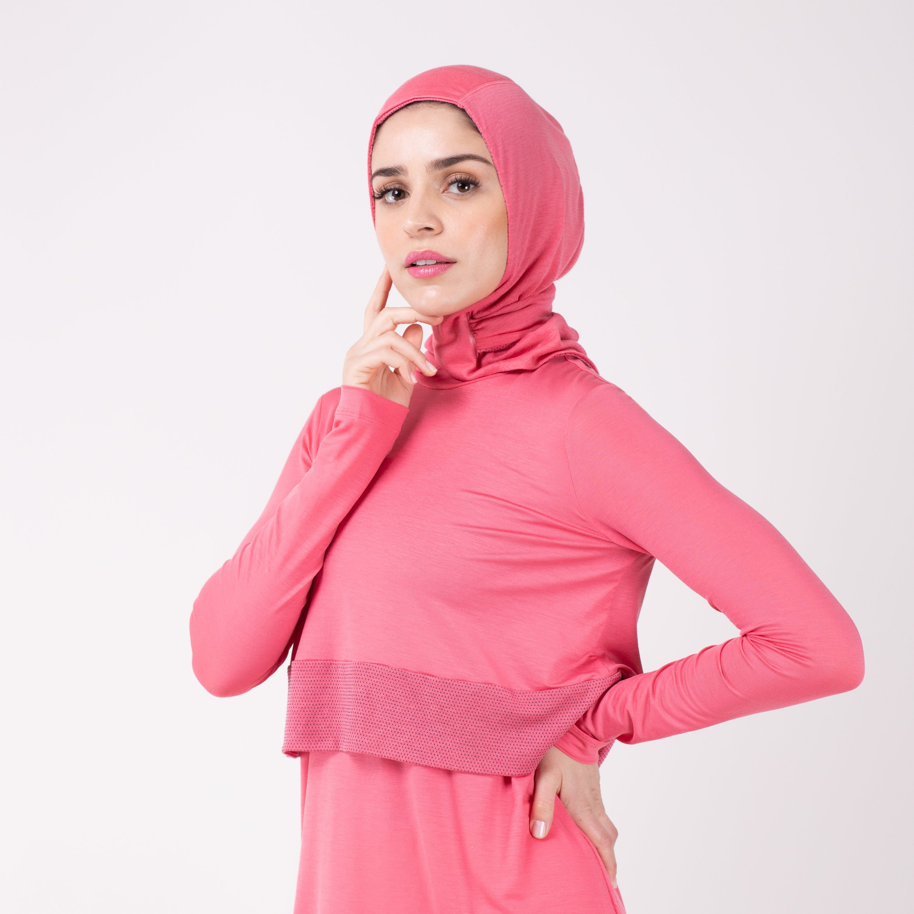 Woman facing left in a pink shirt with a matching pink HAWA hijab, touching her face with her right and and her left hand on her hip.