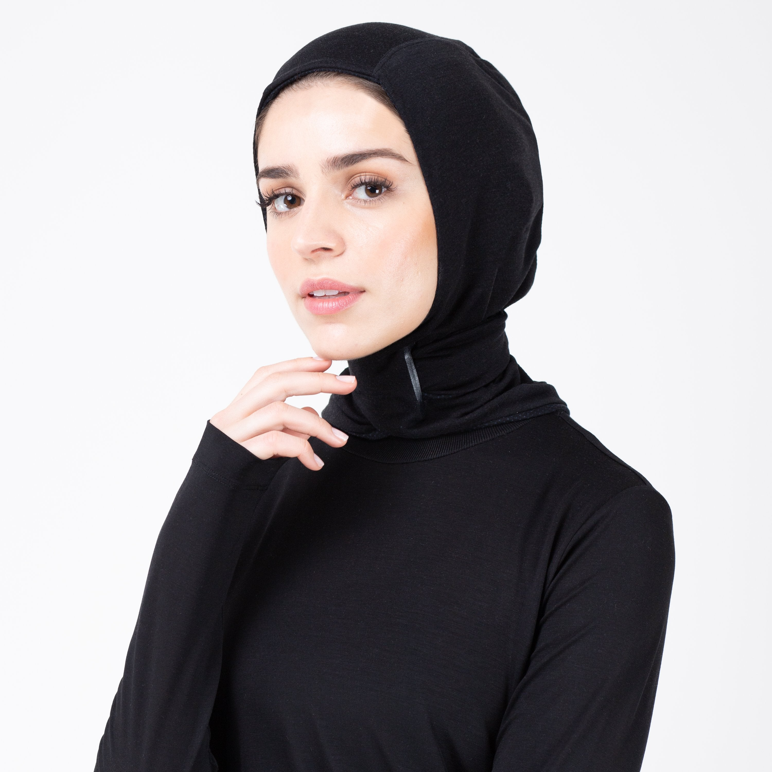 Woman facing left in black shirt and matching black HAWA hijab touching her face.